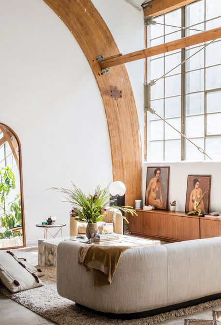 a catchy living room with wooden beams, a curved sofa, a marble coffee table and creative artworks