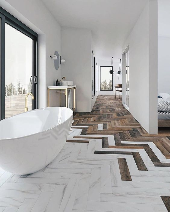 a refined bathroom with wood and white marble tiles with a chevron pattern, a chic tub by the glazed wall