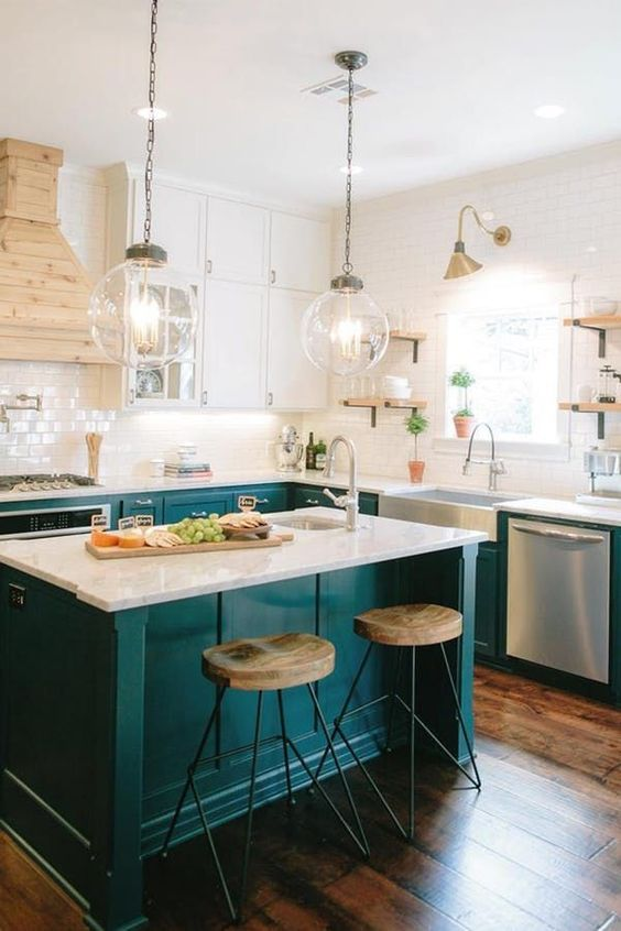 a welcoming farmhouse kitchen with white and emerald kitchen, a white subway tile backsplash and a wooden hood