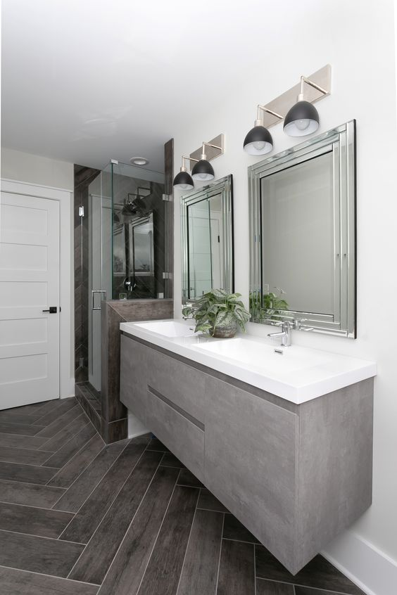 a chic bathroom with a grey sleek floating vanity, a shower space and a couple of mirrors on the wall