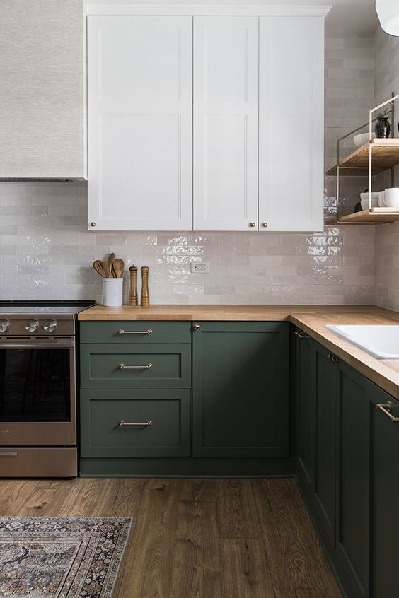 a laconic dark green and white kitchen, with glossy white marble tiles, a butcherblock countertop and simple fixtures