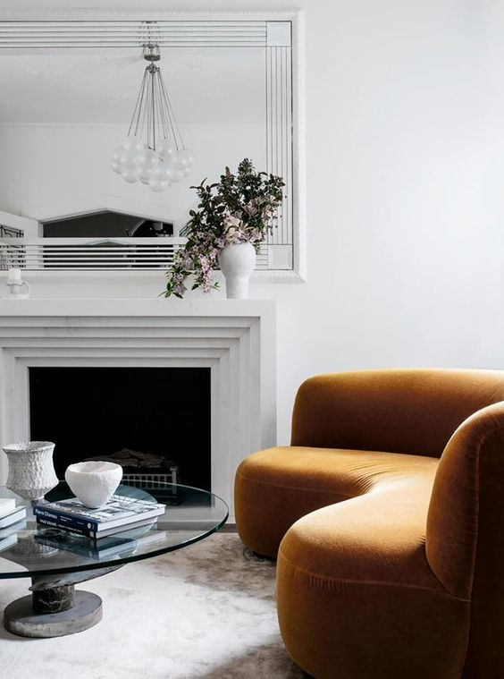 68 a refined living room with a fireplace, a rust-colored curved sofa, a mirror, a round glass table