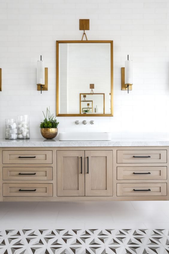 a modern farmhouse bathroom with geometric tiles on the floor, a large wooden floating vanity and a mirror