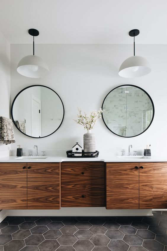 a modern bathroom with grey hex tiles on the floor, a rich-toned floating vanity and round mirrors
