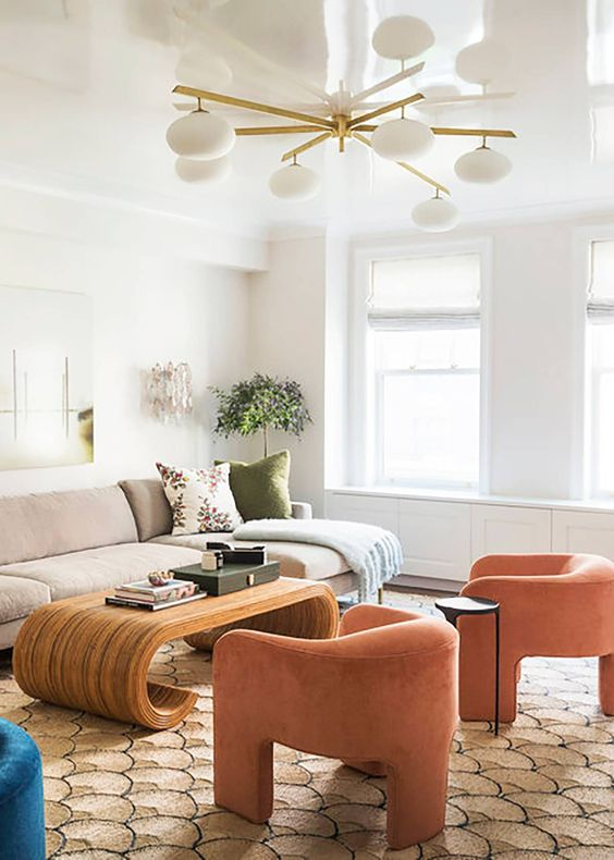 71 a neutral living room spruced up with bright furniture and decor, with orange curved chairs and a creative curved coffee table