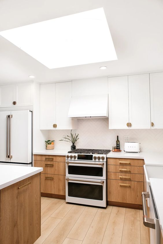 a two tone kitchen with white and ligth stained cabinets, a white chevron tile backsplash and countertops