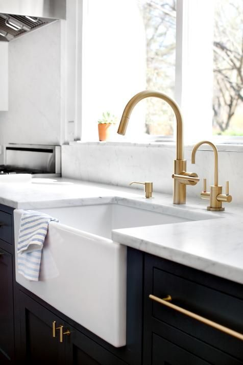 a black and white kitchen accented with gold fixtures and appliances is a stylish and shiny idea