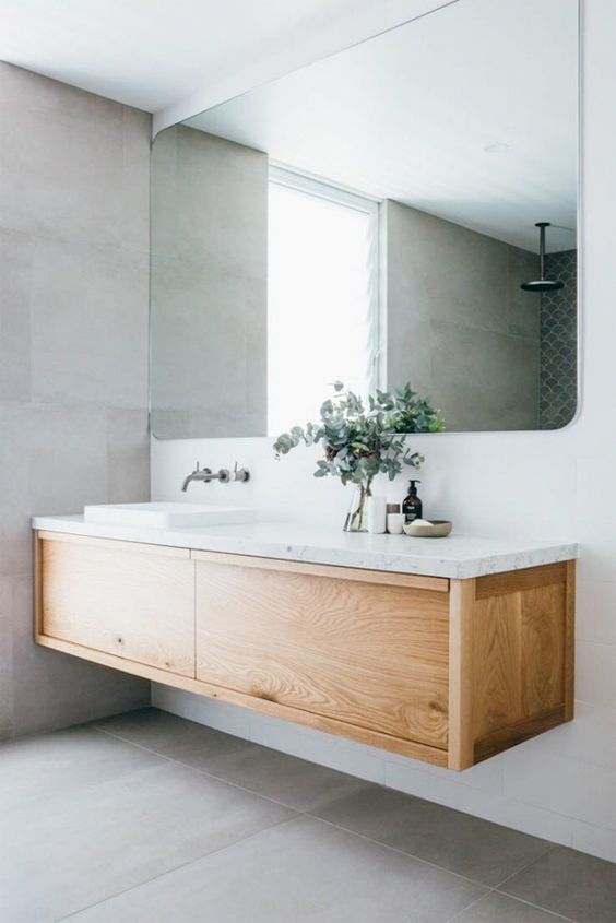 72 a contemporary bathroom with a wood and stone floating vanity, a large mirror and large scale grey tiles