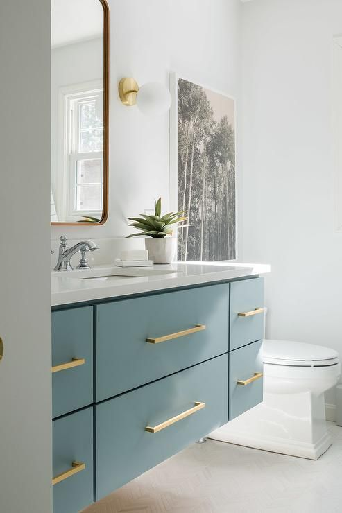 a small bathroom in neutrals, with a floating blue vanity, gold touches and a mirror with curved corners