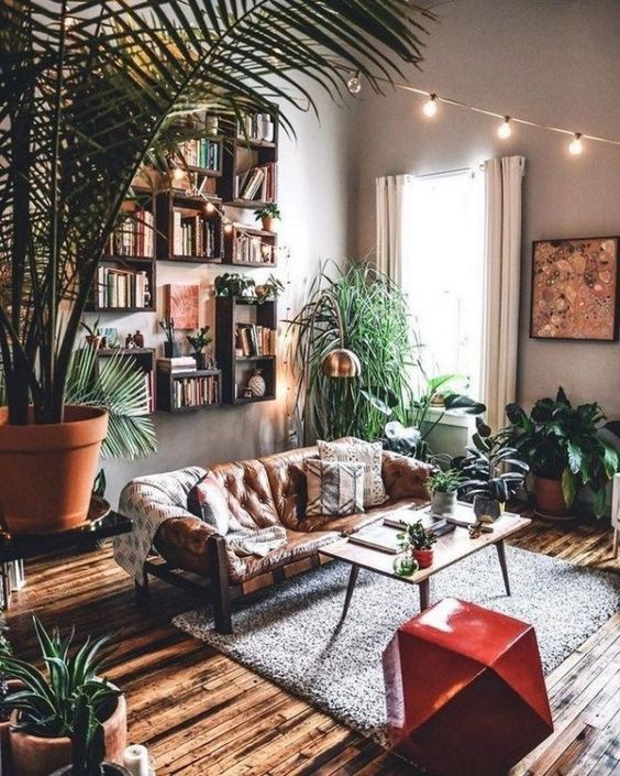 a welcoming modern and boho living room with open box shelves, a leather sofa, a red faceted stool, potted greenery