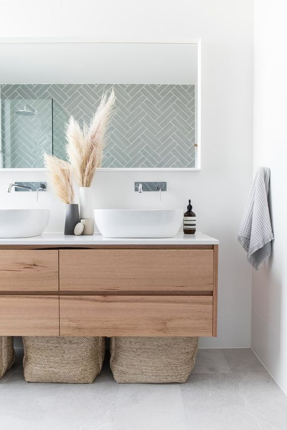 a boho bathroom with a sleek wooden floating vanity, baskets for storage, a long mirror and pampas grass in vases