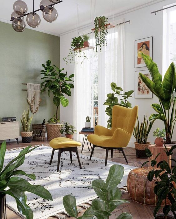 an inviting boho and modern living room with a green accent wall, a yellow chair and lots of potted plants everywhere