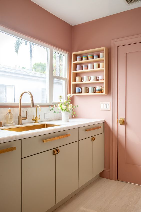 a beautiful Scandinavian kitchen with pink walls and grey cabinets, brass fixtures and a brass sink