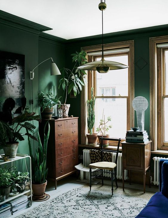 75 a green living room with vintage furniture, potted greenery and various lamps is a very chic space