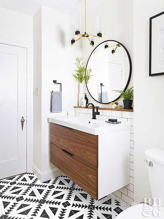 a small modern bathroom with white and black and white tiles, a floating vanity in white and rich stained wood, a round mirror