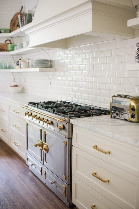 a beautiful vintage kitchen in white, with a white subway tile backsplash and gold fixtures for a more elegant feel