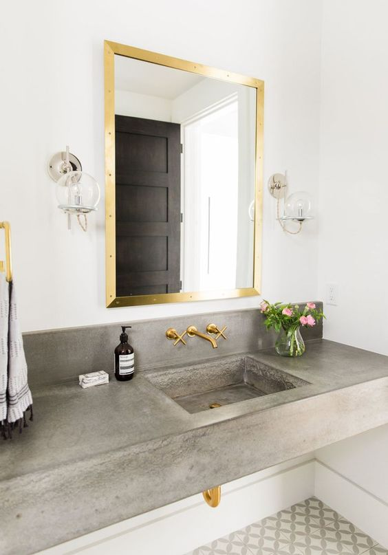 a concrete floating vanity with a built in sink and gold fixtures that soften the look and make the bathroom cooler