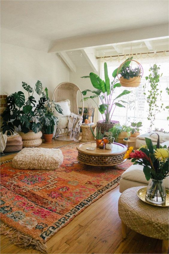80 a boho living room with neutral furniture, a statement rug, lots of potted plants and woven ottomans