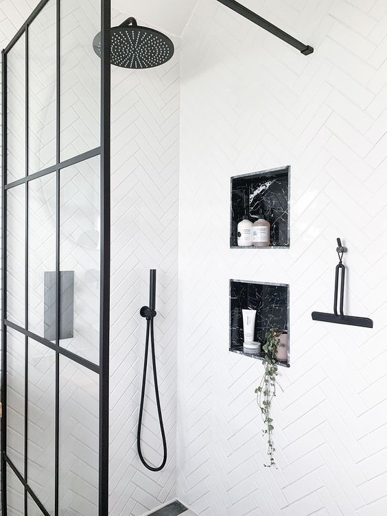 a white bathroom accented with black fixtures and grey marble niches in the shower space