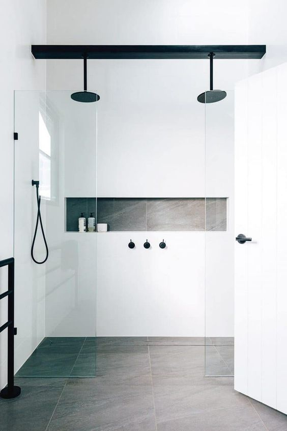 a minimalist white and grey bathroom accented with black fixtures looks more interesting and chic