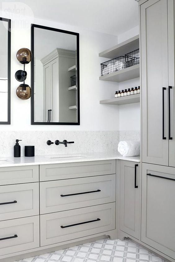 a chic grey bathroom with a patterned tile floor, black fixtures and mirrors in black frames