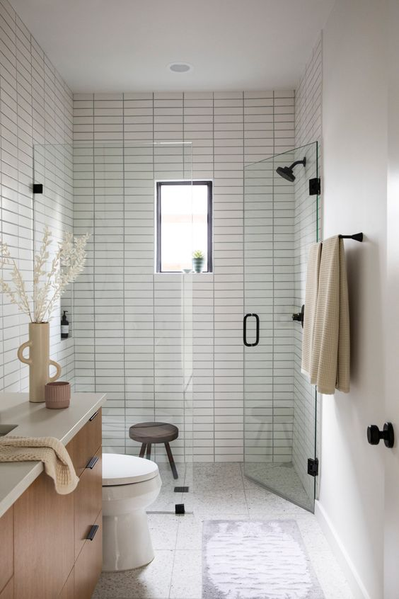 a small and cozy bathroom with skinny tiles, a wooden floating vanity and black fixtures is chic
