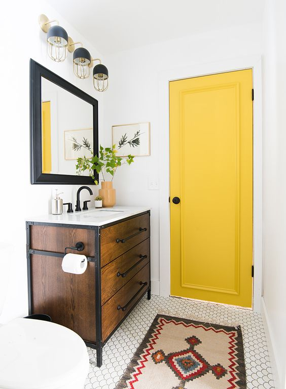 84 a small and bright bathroom with a yellow door for a touch of color and black fixtures to contrast it