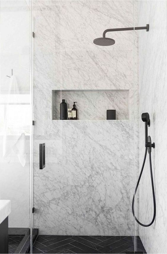 an exquisite white marble bathroom with a black chevron tile floor and black fixtures for a chic look