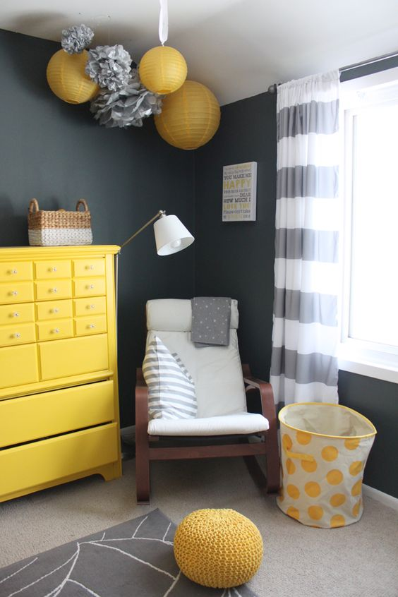 a black, white and yellow nursery with paper lamps and pompoms, a yellow dresser, a rocker, a basket and a knit ottoman plus striped curtains