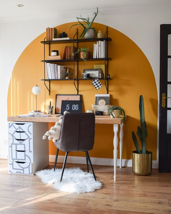 a boho working space with a color block yellow wall, a desk with a cork top, a cofy chair, an open shelving unit and some cacti