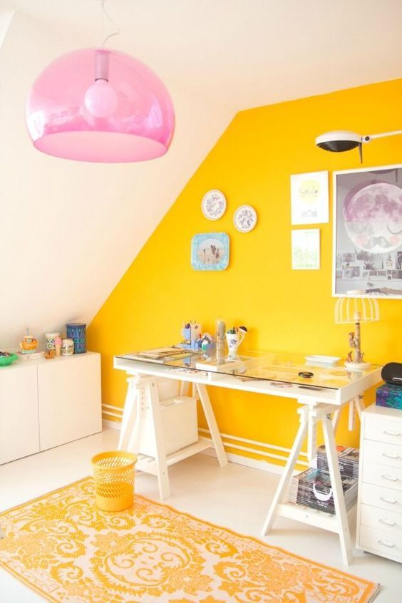 a bold and shiny craft room with a sunny yellow accent wall, white furniture, a pink pendant lamp and pretty artworks