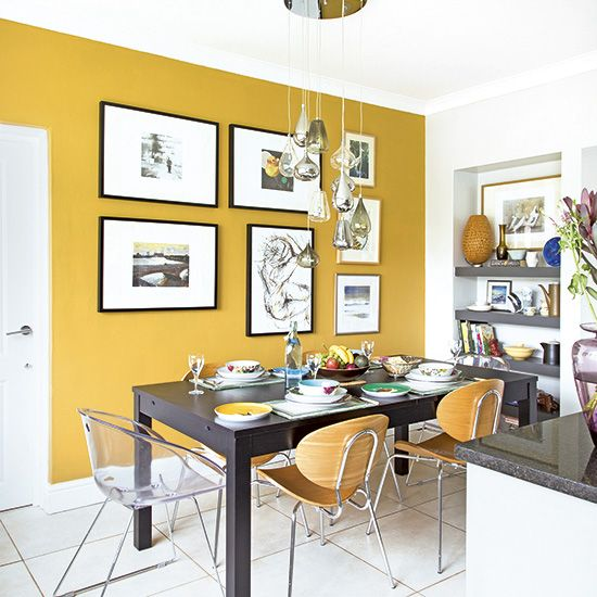a bold modern dining room with a mustard accent wall, a black table, some pretty chairs, niche shelves and a chic gallery wall