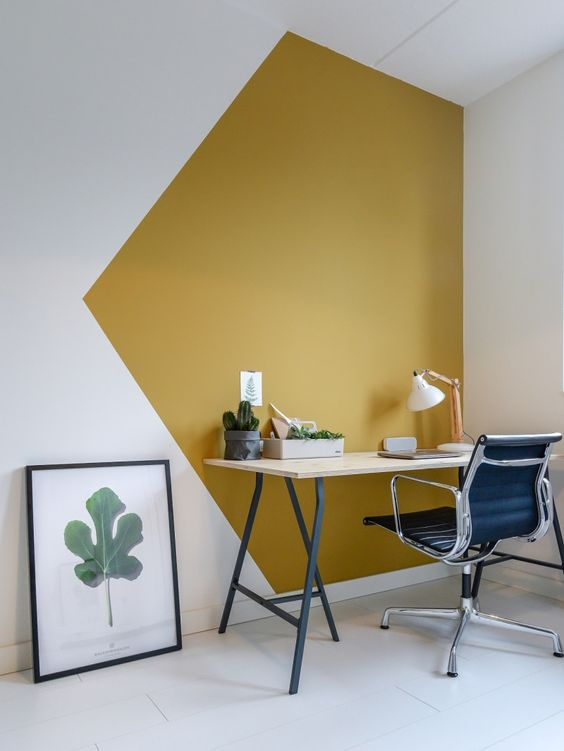 a bold modern working nook with a mustard and white color block wall, a lightweight desk, a black chair and a greenery print