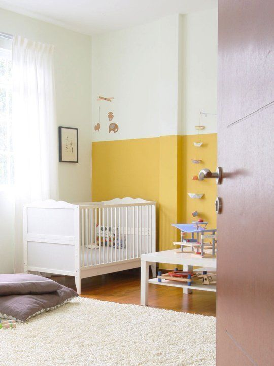 a bold nursery with a mustard and white color block wall, white furniture, colorufl toys and lilac pillows and white textiles