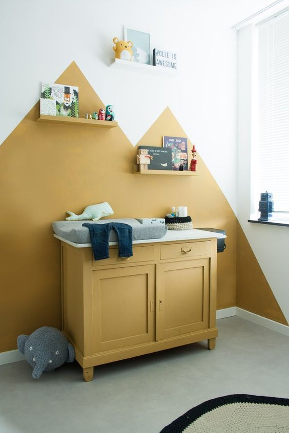 a bold nursery with mustard color blocking on the wall, a mustard cabinet, shelves, toys and artworks and grey touches