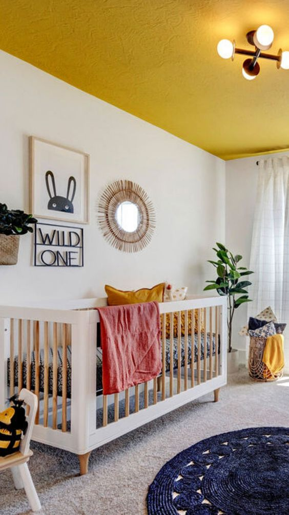 a bright and fun nursery with a yellow ceiling, some yellow linens, layered rugs, a crib and a pretty gallery wall in boho style