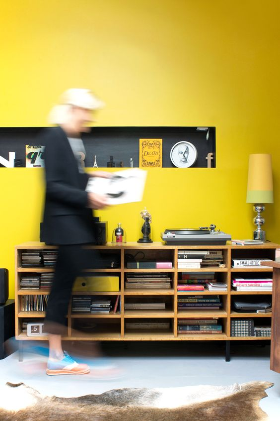 a bright living room with a shiny yellow accent wall, a niche shelf, a vintage sideboard and a bold yellow table lamp