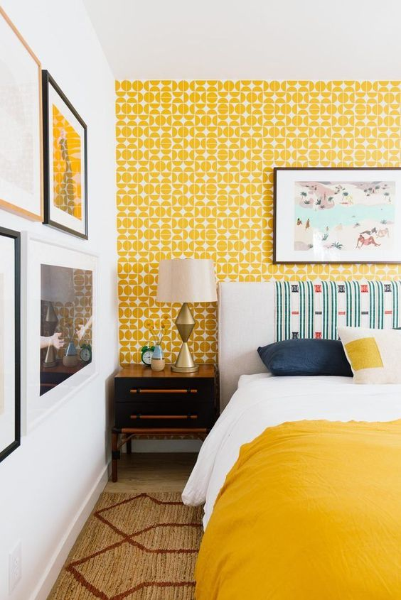 a bright retro bedroom with yellow wallpaper, a bold bed and bedding, a pretty gallery wall and vintage lamps