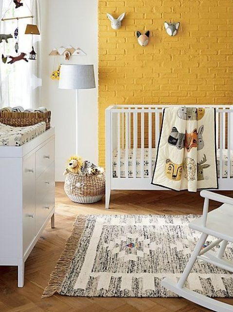 a cheerful nursery with a yellow brick wall, white furniture, a printed rug, funny taxidermy and a mobile plus baskets