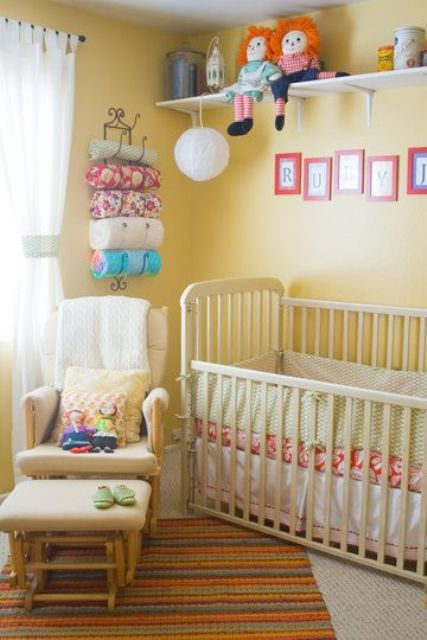 a cheery yellow nursery with vintage furniture, a shelf with toys, colorful textiles and bedding and a comfy chair with a footrest