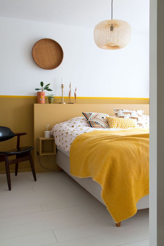 a chic contemporary living room with a mustard accent wall, a yellow and grey bed, bold yellow bedding, a wooden plate and a wicker lamp