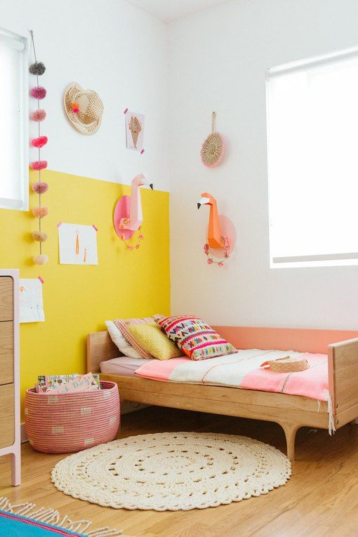 a colorful girl's room with a color block yellow wall, a simple bed and pink bedding, a pink basket, cardboard flamingo heads and other decor