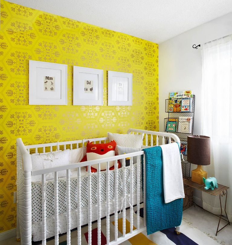 a colorful nursery with a bold yellow wallpaper wall, a white crib, wire shelf, colorful textiles and bedding plus a gallery wall