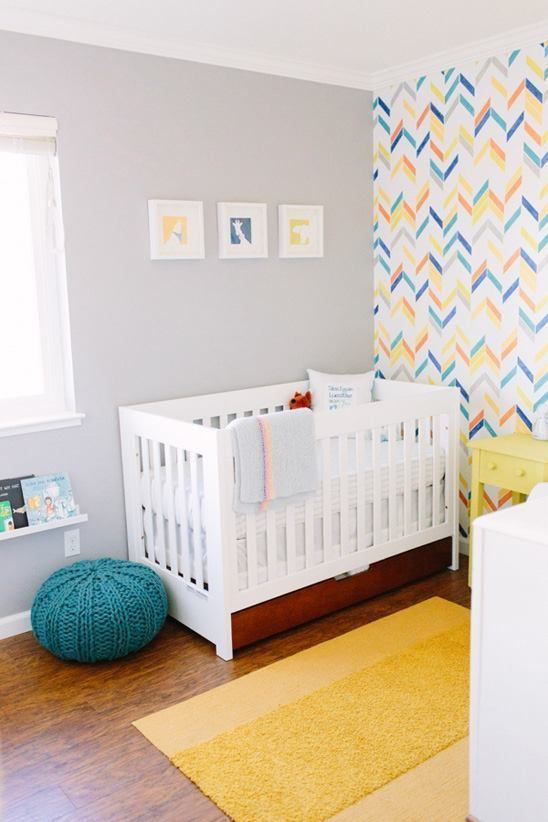a colorful nursery with a bright geometric wall, white and yellow furniture, a yellow rug, a blue ottoman and a gallery wall