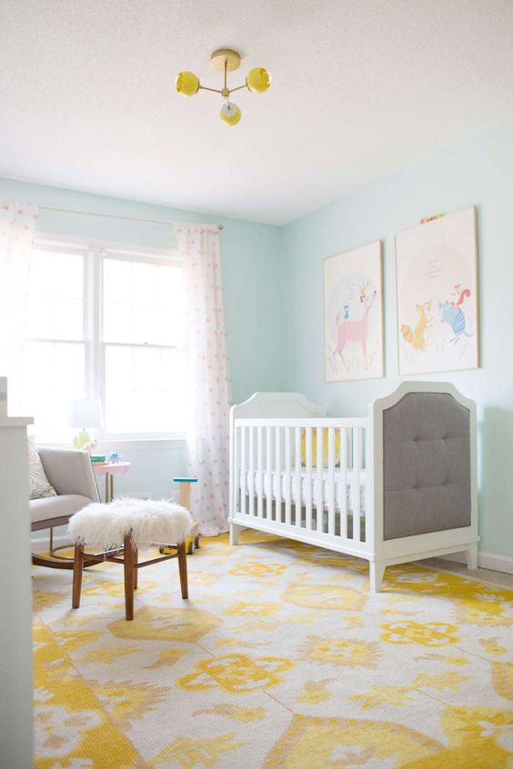 a colorful nursery with light blue walls, neutral furniture, a colorful gallery wall, a printed rug and curtains plus a yellow chandelier