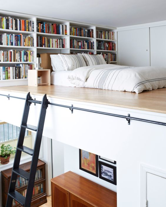 a contemporary apartment with a loft bedroom, built-in bookshelves and a mattress right on the wall