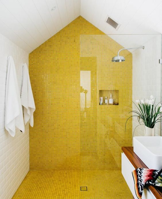 a contemporary bathroom with a bold yellow tile wall and floor in the shower to make this space bolder and catchier