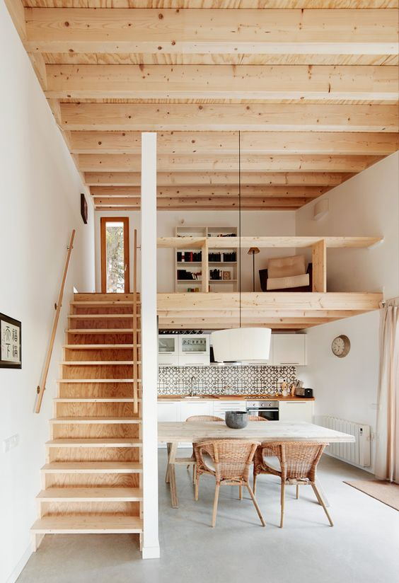 a contemporary home with a wooden ceiling and a staircase, with a kitchen down and a loft reading space with built-in shelves