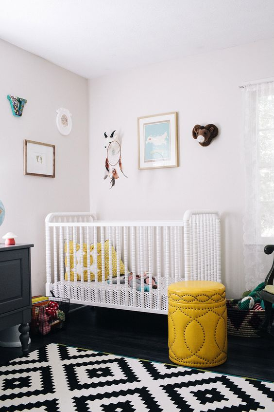 a contrasting nursery in black and white, with black and white furniture, yellow touches and a pretty gallery wall
