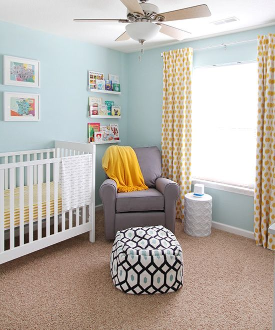 a cozy nursery with light blue walls, a white crib, a grey chair, yellow linens and ledges with books and artworks